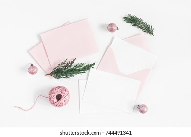 Christmas composition. Envelopes, christmas pink decorations, cypress branches on white background. Top view, flat lay, copy space