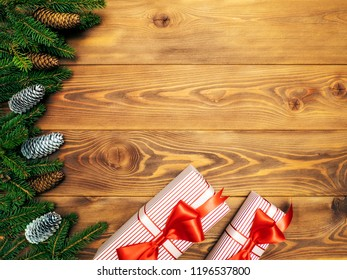 Christmas composition. Fir branches with cones along with gift boxes on the wooden background. Top view. Holiday concept