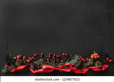 Christmas composition of fir branches, pine cones, berries, and red slack, on black stone background. Xmas and Happy New Year theme. Flat lay, top view