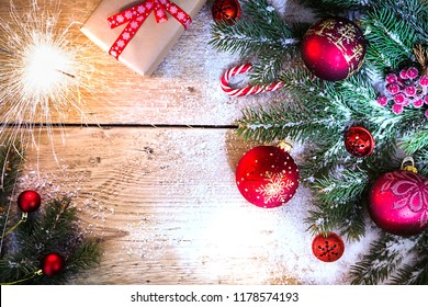 Christmas composition with fir tree branches and christmas decorations on wooden background, top view with copy space