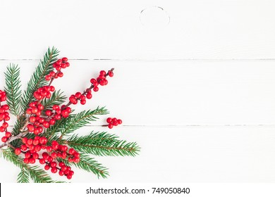 Christmas composition. Fir tree branches and red berries on white background. Christmas, winter, new year concept. Flat lay, top view, copy space