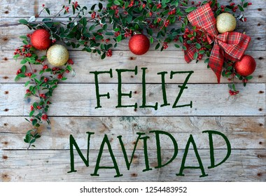 "Christmas composition frame with ""Feliz Navidad"" for postcard. Balls, checked tie and green foliage with berries. background translation merry chrimas"