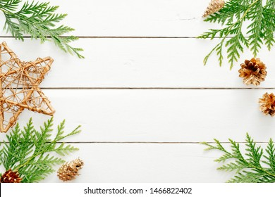 Christmas composition. Frame made of Christmas decorations and fir tree branch on wooden white table. Flat lay, top view, copy space. Christmas, New Year, winter holiday concept. Postcard template.