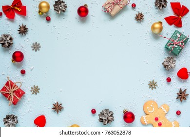 Christmas composition. frame made of christmas decorations, red berries, gift boxes and pine cones on blue background. Christmas background. Flat lay. top view with copy space