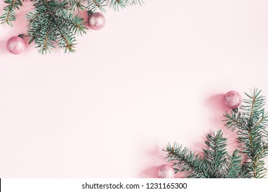 Christmas composition. Frame made of fir tree branches, pink balls on pastel pink background. Christmas, winter, new year concept. Flat lay, top view, copy space