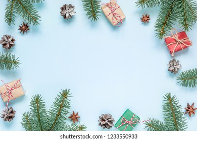 christmas composition. frame made of fir branches, star anise, decorations, gift boxes and pine cones on blue background. Xmas background. Flat lay. top view with copy space