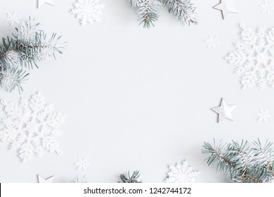 Christmas composition. Frame made of fir tree branches, decorations on pastel gray background. Christmas, winter, new year concept. Flat lay, top view, copy space