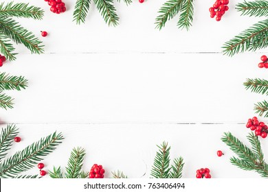 Christmas composition. Christmas frame made of fir tree branches and red berries on white background. Flat lay, top view, copy space