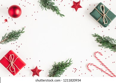Christmas composition. Frame made of gifts, fir tree branches, red decorations on white background. Christmas, winter, new year concept. Flat lay, top view, copy space