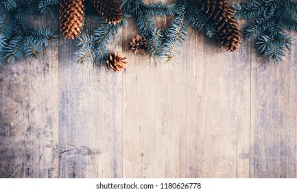 Christmas composition. Frame made of pine branches, fir cones on rustic vintage wooden background. Flat lay, top view, copy space.