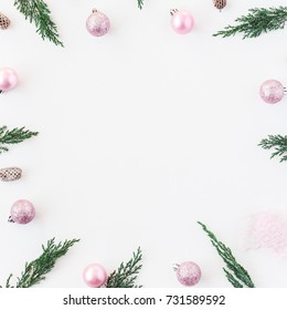 Christmas composition. Christmas frame made of pine branches, pink balls, pine cones on white background. Flat lay, top view, copy space, square