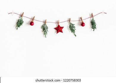 Christmas composition. Garland made of red balls and fir tree branches on white background. Christmas, winter, new year concept. Flat lay, top view, copy space