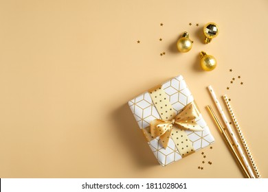Christmas composition. Gift box, golden balls decorations, drinking straws on yellow background. Christmas party invitation card mockup