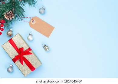 Christmas composition with gift box, pine branch, empty shopping tag and festive balls, on a blue background, horizontal, copy space, top view