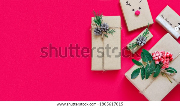 Christmas composition of gift boxes in craft paper on a red background.The concept of zero waste.Eco-friendly natural decor for packaging Christmas gifts.flat lay.copy space.banner