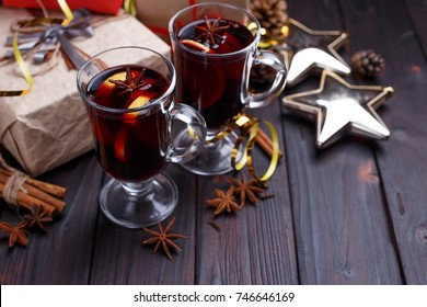 Christmas composition with gift boxes, mulled wine, baubles and decorations on dark wooden background. Christmas eve, New year celebration concept