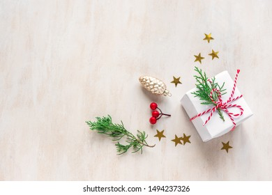 Christmas composition. Christmas gift, fir branches and golden stars on white wooden background. Flat lay, top view, copy space.