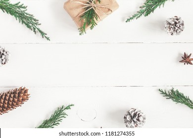 Christmas composition. Gift, fir tree branches on white wooden background. Christmas, new year, winter concept. Flat lay, top view, copy space