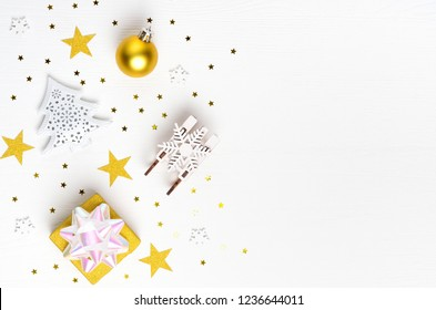 Christmas composition. Gift, gold and white decorations on white background. Christmas, winter, new year concept. Flat lay, top view, copy space.
