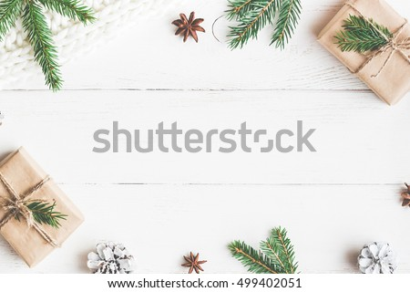 Christmas composition. Christmas gift, knitted blanket, pine cones, fir branches on wooden white background. Flat lay, top view, copy space