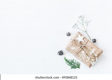Christmas composition. Christmas gift, pine cones, thuja branches and gypsophila flowers. Top view, flat lay, copy space