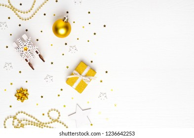Christmas composition. Gift, sleigh, gold decorations on white background. Christmas, winter, new year concept. Flat lay, top view, copy space.