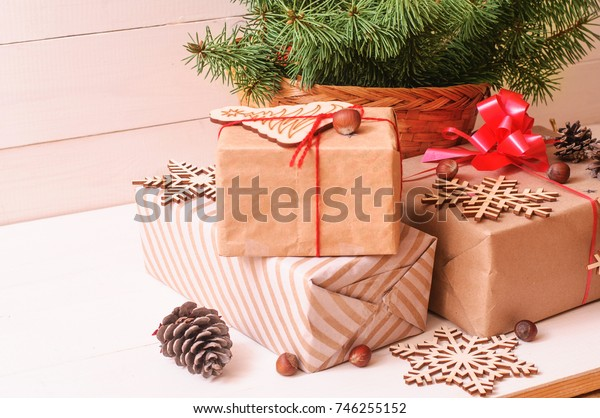 Christmas composition. Christmas gift, wooden snowflakes, pine cones, fir branches on wooden  white background. Flat lay, top view