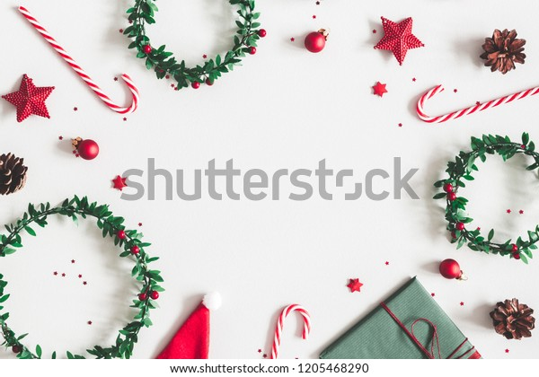 Christmas composition. Gift, wreaths, red decorations on pastel gray background. Christmas, winter, new year concept. Flat lay, top view, copy space