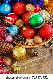 Christmas Composition with Gifts. Basket, red balls, pine cones, snowflakes on Wooden Table. Vintage style. toning