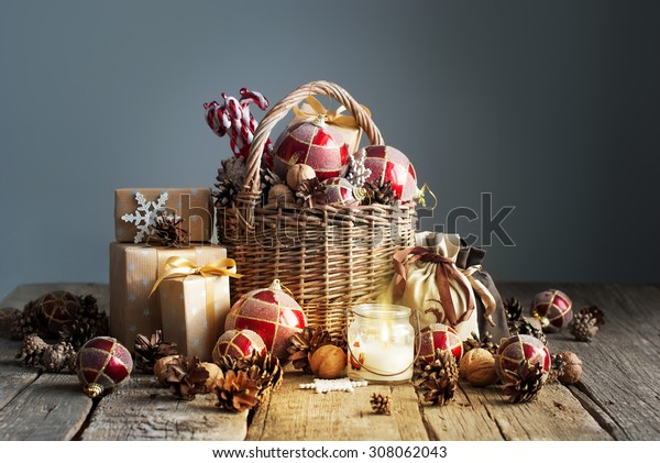 Christmas Composition with Gifts and Burning Candle. Basket, red balls, pine cones, snowflakes on Grey Background. Vintage style