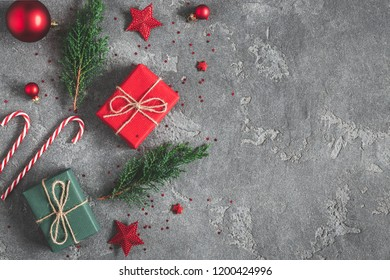 Christmas composition. Gifts, fir tree branches, red decorations on black background. Christmas, winter, new year concept. Flat lay, top view, copy space