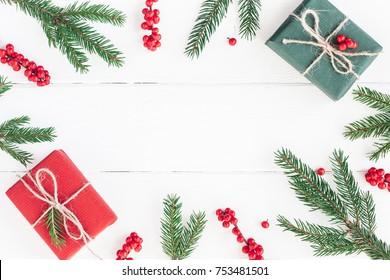 Christmas composition. Christmas gifts, fir tree branches and red berries on white wooden background. Flat lay, top view, copy space