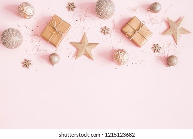 Christmas composition. Christmas gifts, golden decorations on pastel pink background. Flat lay, top view, copy space
