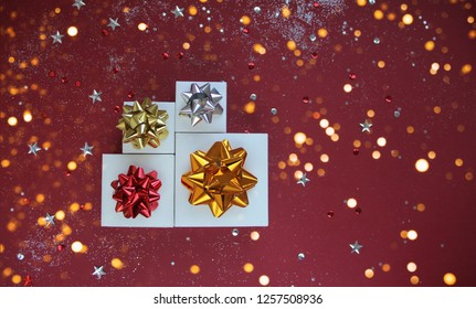 Christmas composition. Gifts on red background with golden festive lights. Christmas, winter, new year concept. Flat lay, top view, copy space.