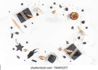 Christmas composition. Christmas gifts, pine cones, black and golden decorations on white background. Flat lay, top view, copy space