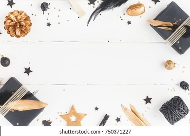 Christmas composition. Christmas gifts, pine cones, black and golden decorations on white wooden background. Flat lay, top view, copy space