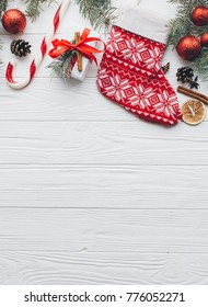 Christmas composition. Gifts, pine cones, fir branches, candy, spices and other decorations on wooden white background. Flat lay, top view.