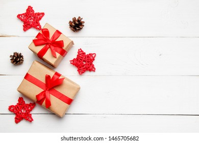 Christmas composition. Christmas gifts with red decorative stars from rattan and cones on wooden white background. Greeting card concept. Top view, flat lay, copy space.
