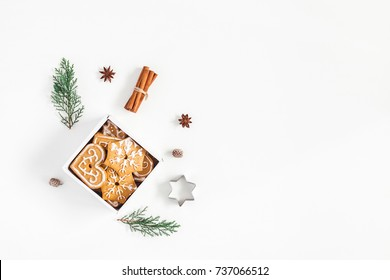 Christmas composition. Christmas gingerbread cookies and pine branches on white background. Flat lay, top view, copy space