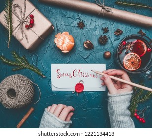 Christmas composition, a girl signs an envelope, toys and New Year's attributes are laid out, a place for text