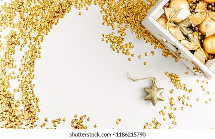 Christmas composition. Gold sequins, a box of Christmas decorations on white background. Flat lay, top view, copy space