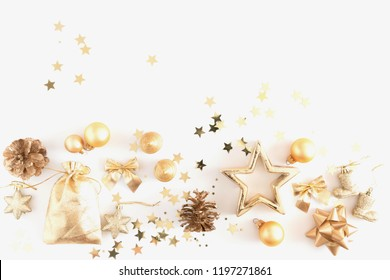 Christmas composition. Christmas golden decorations, pine cone, star, balls on white background. Flat lay, top view, copy space