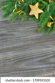 Christmas composition with green fir branches and golden decorations on a wooden background, wish copy-space