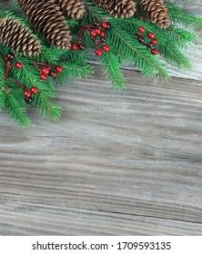 Christmas composition with green  fir branches, fir cones and red holly berries on a wooden background, with cjpy-space