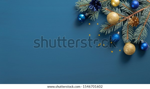 Christmas composition with green pine twigs, gloden and blue decorations, confetti on blue background with copy space. Top view, Flat lay. Xmas banner mockup, vintage postcard template