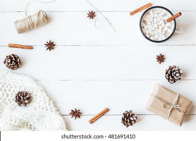 Christmas composition. Hot chocolate, cinnamon sticks, anise star, marshmallow, knitted blanket, gift and cones on wooden white background. Winter, christmas concept. Flat lay, top view