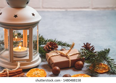 Christmas composition - lantern with burning candle and traditional ornaments.
