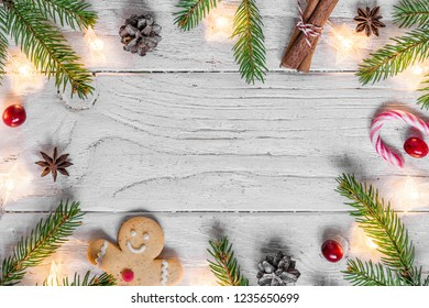 Christmas composition with christmas lights, food, fir tree, berries and pine cones on white wooden background with copy space for your text. top view. flat lay