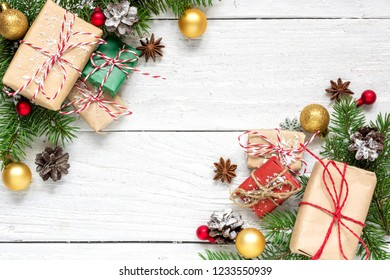 christmas composition made of fir branches, gift boxes, decorations and pine cones on white wooden table covered with snow. Christmas background. Flat lay. top view with copy space
