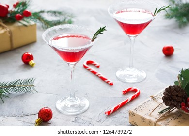 Christmas composition with martini drinks with rosemary and sugar decoration, fir-trees, balls candy canes craft gift box in red colors gray concrete background. Winter holiday, New Year party concept
